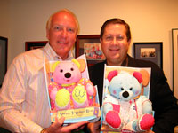 Mark Victor Hansen and Robert G. Allen coauthors of The One Minute Millionaire, display their delight in the Always Together Bear mentioned in their book and manifested as a real toy for children of all ages. The Always Together Bear will start arriving in major toy stores, January 15, 2003.